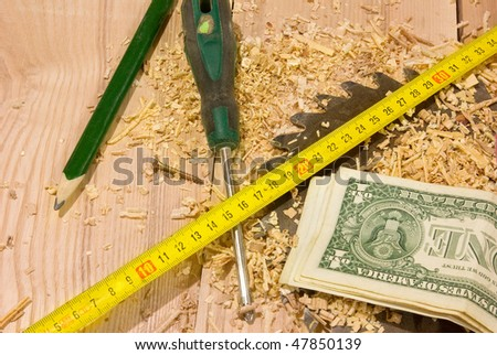 American dollars lying on the sawdust and pencil, tape-measure, circular saw - stock photo