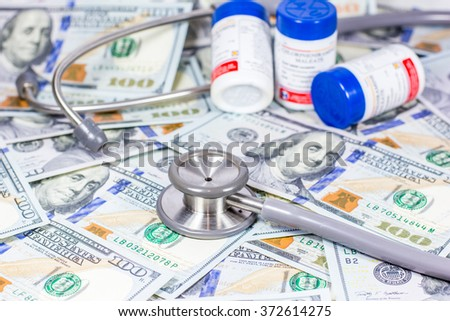 American dollars with stethoscope costs for the medical insurance,Focus on stethoscope and blurry background - stock photo
