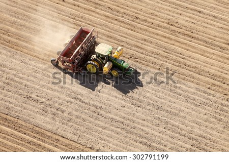 American Falls, Idaho, USA Apr. 17, 2015 An aerial view of farm machinery planting potatoes in the fertile farm fields of Idaho. - stock photo