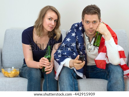 American fans watching sports match on tv. - stock photo