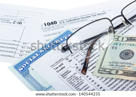 American federal tax form 1040 with money and social security card isolated on white.