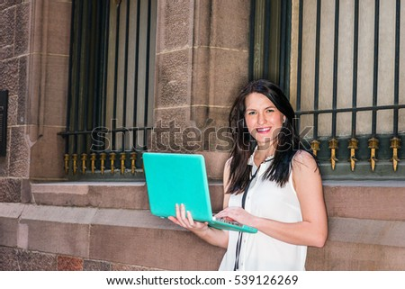American female college graduate student studying in New York, wearing white sleeveless shirt, standing against vintage wall on street, working on laptop computer, smiling. Color filtered effect.