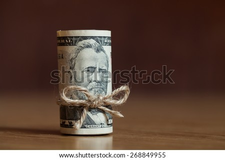 American Fifty Dollar Bills rolled up with a thread on the woode