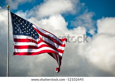 American flag against a cloudy sky on a windy day - stock photo