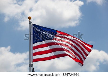 American flag against blue sky with clouds - stock photo