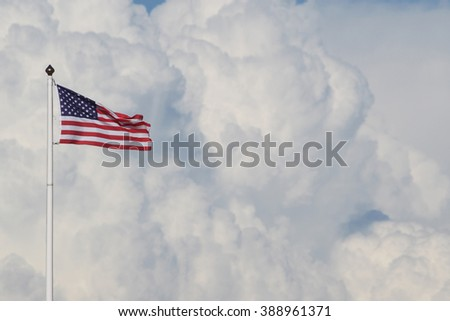 American flag against white clouds. - stock photo