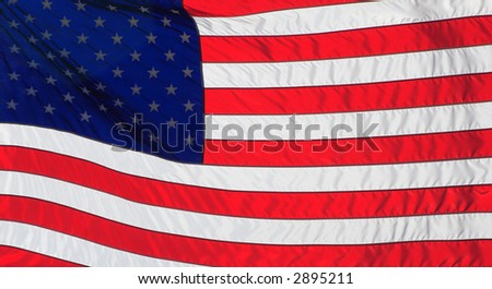 American Flag backlit by the sun and blowing in the wind - stock photo