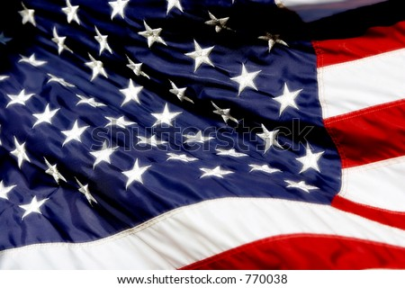 American Flag billowing in the wind, with high color and radiant whites. - stock photo