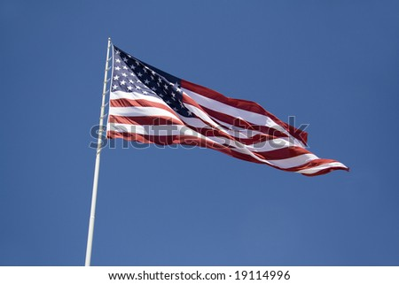 American flag blowing high in the Nevada desert wind against a clear blue sky