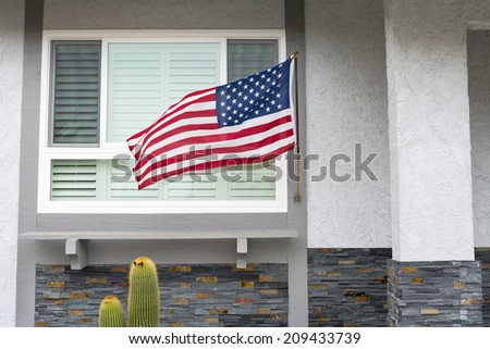 American flag blowing in the breeze while hanging on a residential home symbolizes a patriotic holiday in the United States.