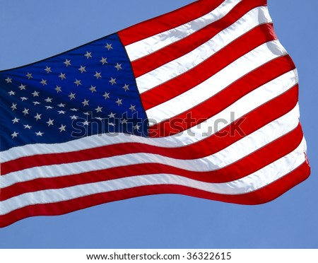 American Flag blowing in the wind against blue sky