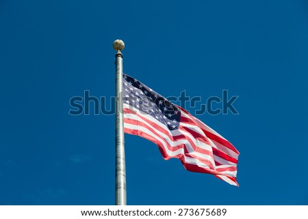 American Flag blowing in the wind at the top of a flagpole - stock photo
