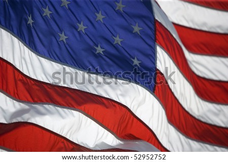 American Flag curls and flaps with a strong breeze - stock photo