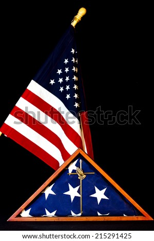 American Flag encased in box with brass praying hands cross in forefront.  Flag in background. - stock photo