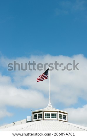 American flag flapping in the wind against sunny sky - stock photo