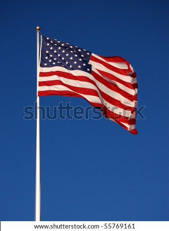 American flag flapping, with clear sky background, vertical - stock photo