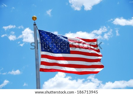 American flag floating in the wind with a blue sky in the background - stock photo