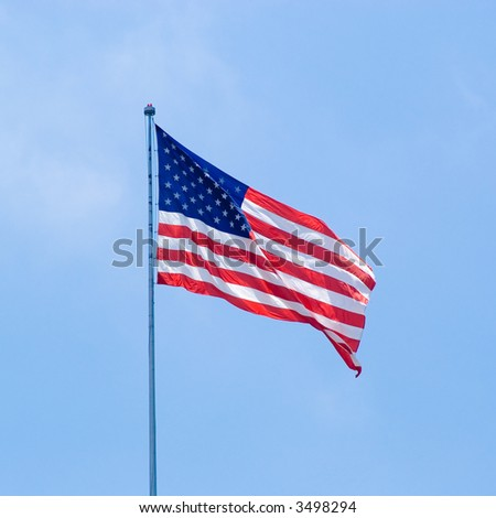 American Flag Flying Against Blue Sky - stock photo