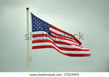 American flag flying at full staff waving in the wind.