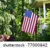 American flag flying from porch in wooded setting. - stock photo