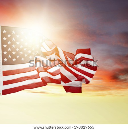 American flag flying in bright sky - stock photo