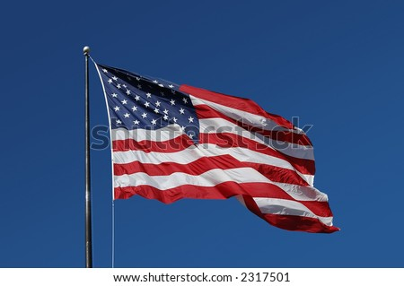 American Flag flying on a blue background - stock photo