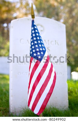 American flag in front of a gravestone in a military cemetery - stock photo