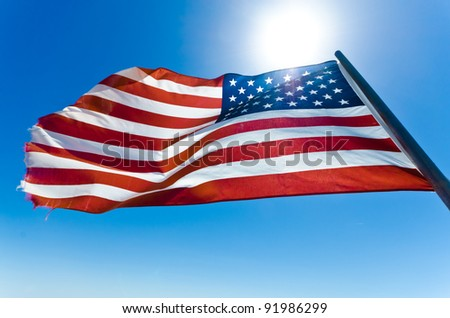 American flag in the clear blue sky - stock photo