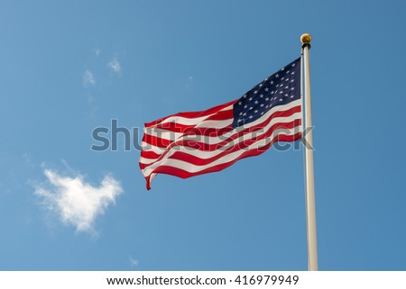 American flag on blue sky with white cloud