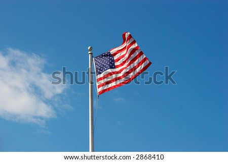 American flag over blue sky wih small white cloud - stock photo