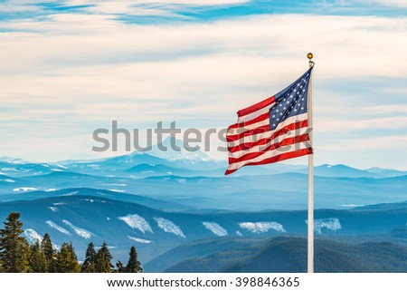 American flag over the peak of snow mountain - stock photo
