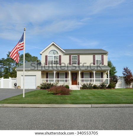American Flag pole Beautiful Suburban McMansion Home Landscaped blue sky clouds residential neighborhood USA - stock photo