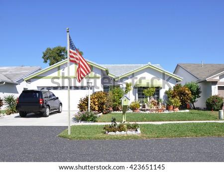 American Flag Pole curbside Beautiful Suburban Ranch Home Sunny residential neighborhood Clear Blue Sky USA - stock photo