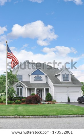 American Flag Pole front yard lawn Suburban McMansion style home Residential Neighborhood USA Blue Sky Clouds - stock photo