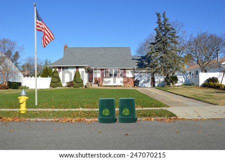 American flag pole Green recycle, reuse, reduce, trash container Suburban brick and siding cape cod style home yellow fire hydrant curbside on autumn clear blue sky day residential neighborhood USA