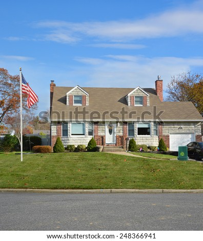 American flag pole Green recycle, reuse, reduce, trash container Suburban Cape Cod home landscaped beautiful autumn day residential neighborhood USA - stock photo