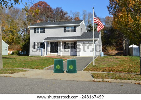 American flag pole Green recycle, reuse, reduce, trash container Suburban Gray High Ranch home autumn day residential neighborhood clear blue sky day USA - stock photo