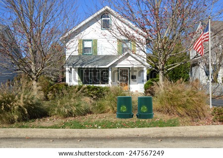 American flag pole Green recycle, reuse, reduce, trash container suburban home ornamental grass autumn day residential neighborhood USA