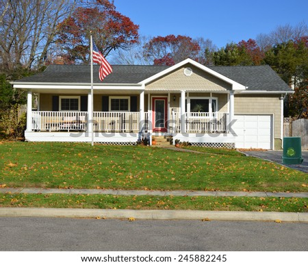 American flag pole Green recycle, reuse, reduce, trash container Suburban Ranch style home with porch sunny autumn day residential neighborhood clear blue sky USA - stock photo