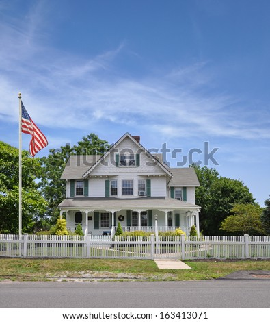American Flag Pole Large Suburban Home with White Picket Fence Sunny Blue Sky Clouds USA Residential Neighborhood - stock photo