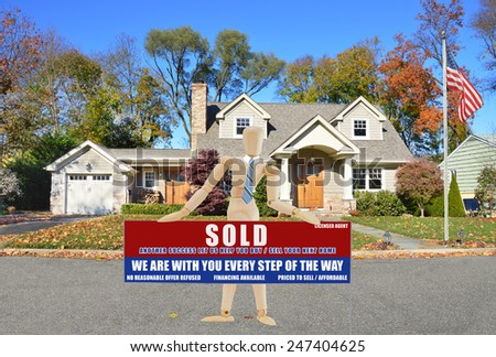 American flag pole Mannequin wearing tie holding Real estate sold (another success let us help you buy sell your next home) sign suburban cape cod style home autumn day residential neighborhood USA - stock photo