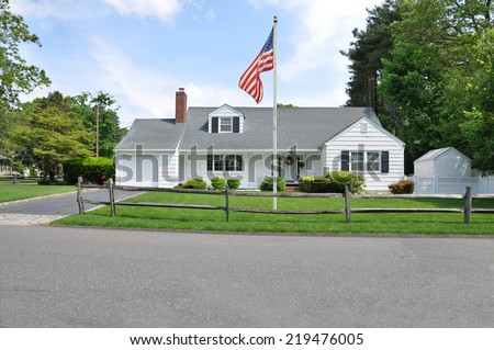American flag pole on front yard lawn of Ranch style Suburban home wood fence residential neighborhood street USA blue sky clouds - stock photo