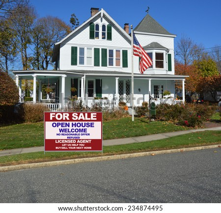 American flag pole Real Estate for sale open house welcome sign curb of suburban gable front Victorian style home in residential neighborhood clear blue sky USA - stock photo