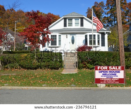 American flag pole Real Estate for sale open house welcome sign Suburban home autumn day residential neighborhood clear blue sky USA - stock photo