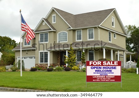 American flag pole Real estate for sale open house welcome sign Suburban McMansion style home overcast cloudy day residential neighborhood USA - stock photo