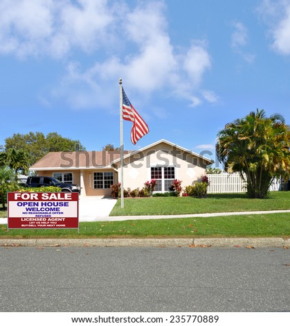 American flag pole Real Estate for sale open house welcome sign suburban ranch style home sunny residential neighborhood blue sky clouds USA - stock photo