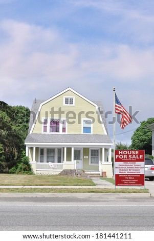 American Flag pole Real Estate For Sale Sign Suburban Gambrel style home residential neighborhood usa blue sky clouds - stock photo