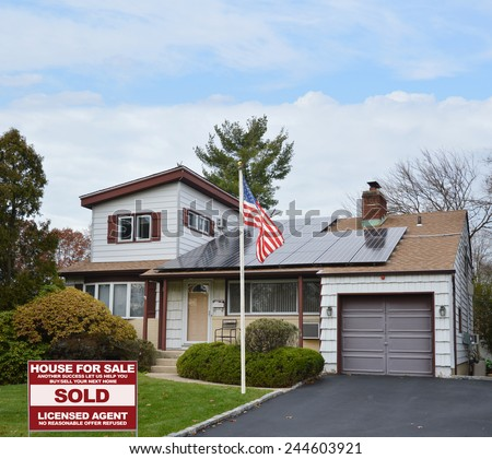 American flag pole real estate sold (another success let us help you buy sell our next home) sign Suburban Ranch style home with solar panel on roof residential neighborhood USA blue sky clouds