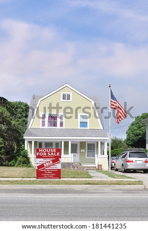 American Flag pole Real Estate Sold (another success let us help you buy sell your next home) Sale Sign Suburban Gambrel Style Home Residential neighborhood usa blue sky clouds - stock photo