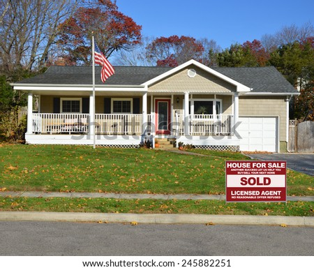 American flag pole Real estate sold (another success let us help you buy sell your next home) sign Suburban Ranch style home with porch sunny autumn day residential neighborhood clear blue sky USA - stock photo